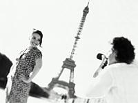 Couple à la tour Eiffel - l'homme prend la femme en photo - cliché noir et blanc
