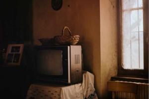 Intérieur d'une ferme. Une fenêtre, une table recouverte d'une toile cirée et un vieux poste de télévision à tube cathodique.