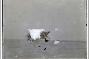 Volutes de matières blanches et grises dans une pièce devant un mur.